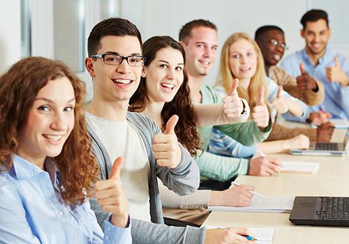 Viele lachende Studenten halten ihre Daumen hoch im Unterricht