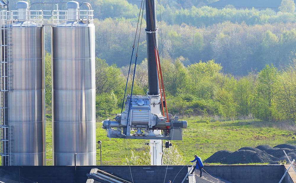 Mit Hilfe eines Spezialkrans wurde die 30 Tonnen schwere Maschine in einer sehenswerten Aktion vom Transporter durch die Dachöffnung gehievt.