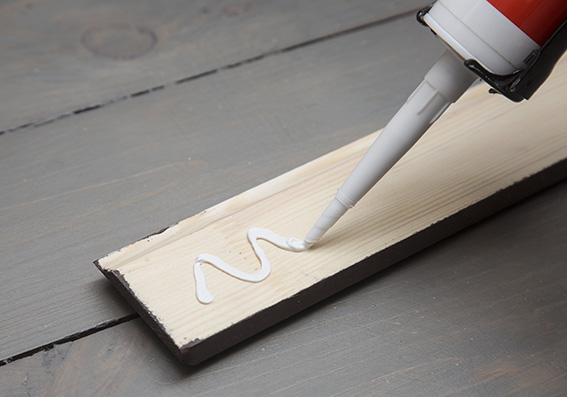 putting glue on a piece of wooden baseboard